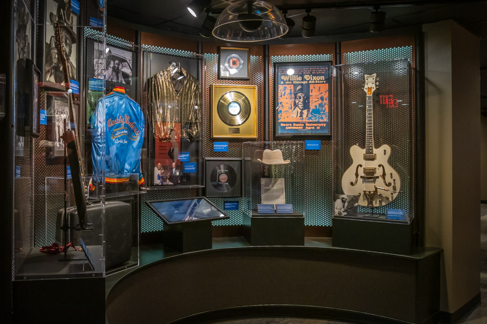 display case with guitar, jacket, albums, and other memorabilia