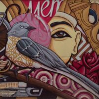 a bird and woman's face on a street mural