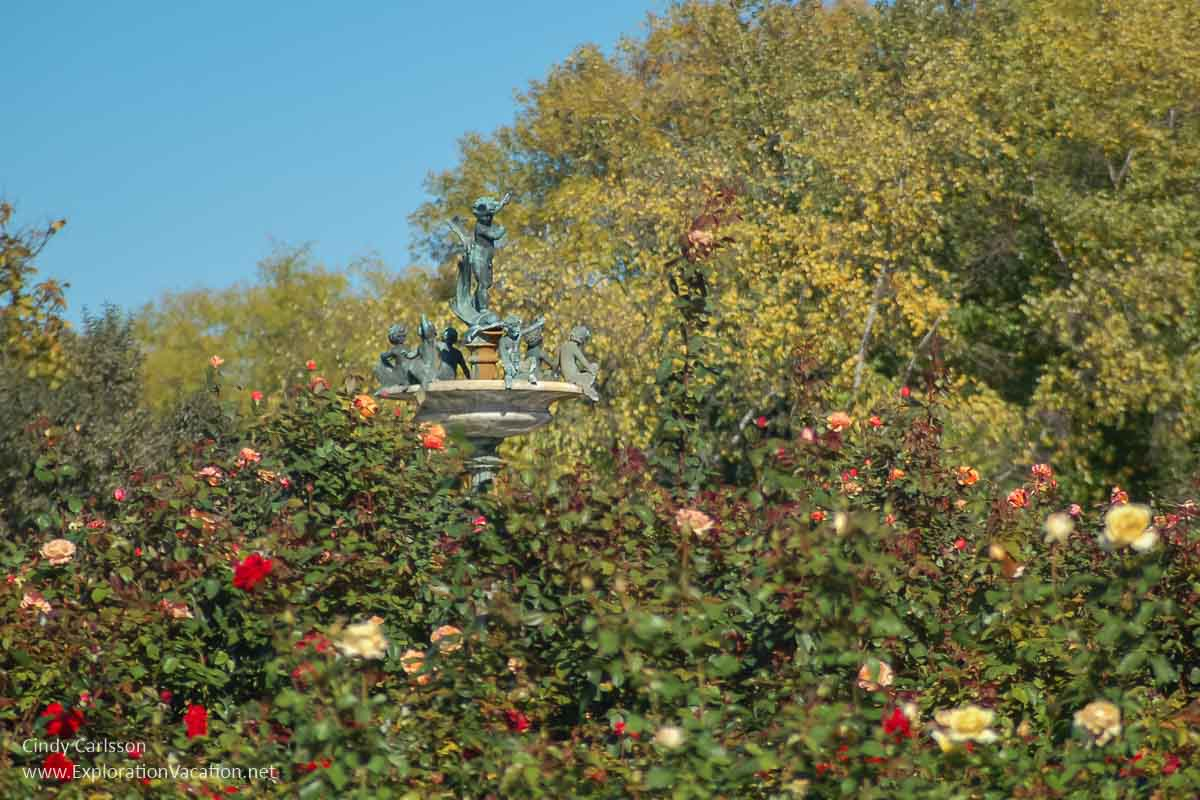 top of fountain with cherub and satyrs above roses