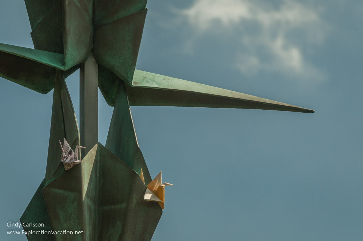detail of sculpture with folded paper cranes tucked into it