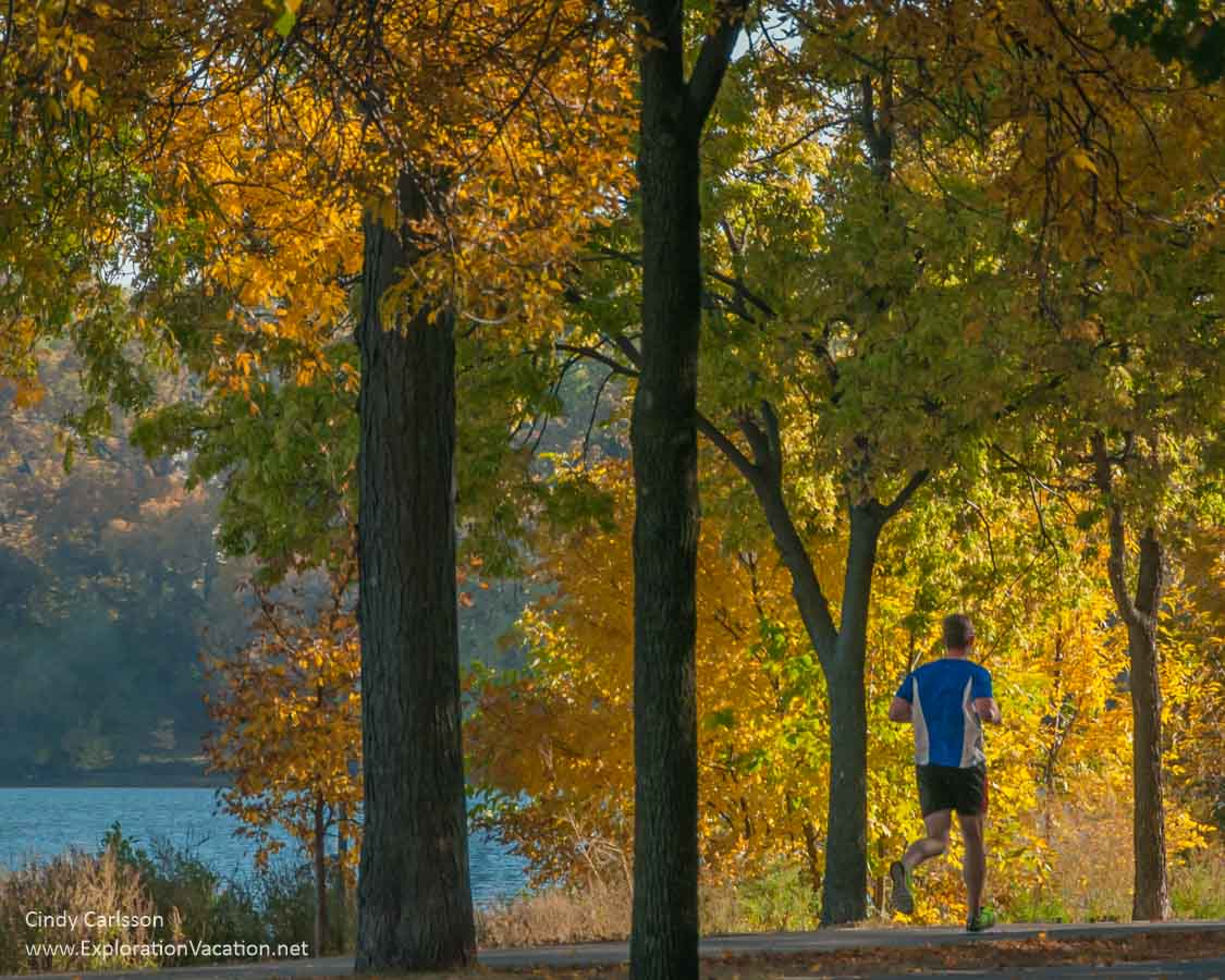 runner framed by golden trees with lake visible to the side
