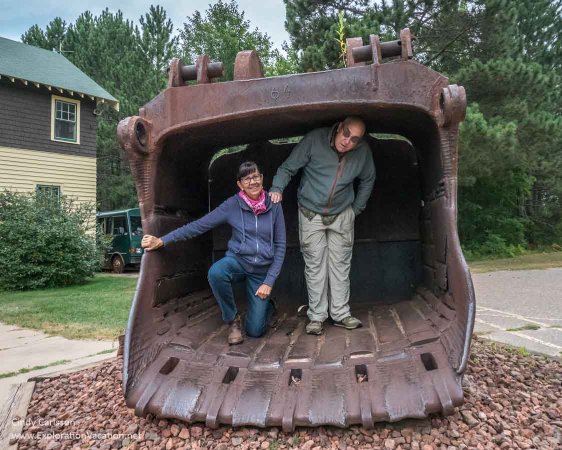 large bucket used to scoop rock with two people standing in it