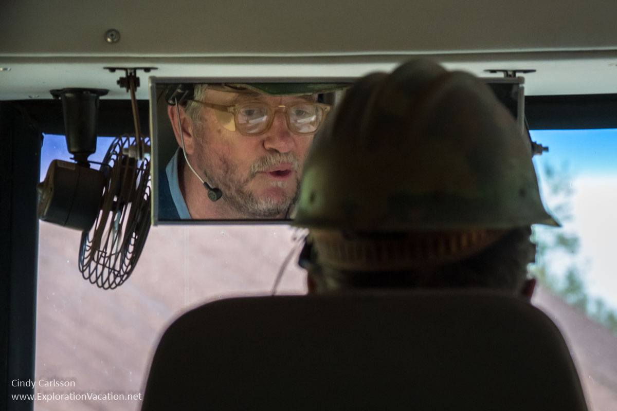 view of bus driver from behind with face visible in rear view mirror