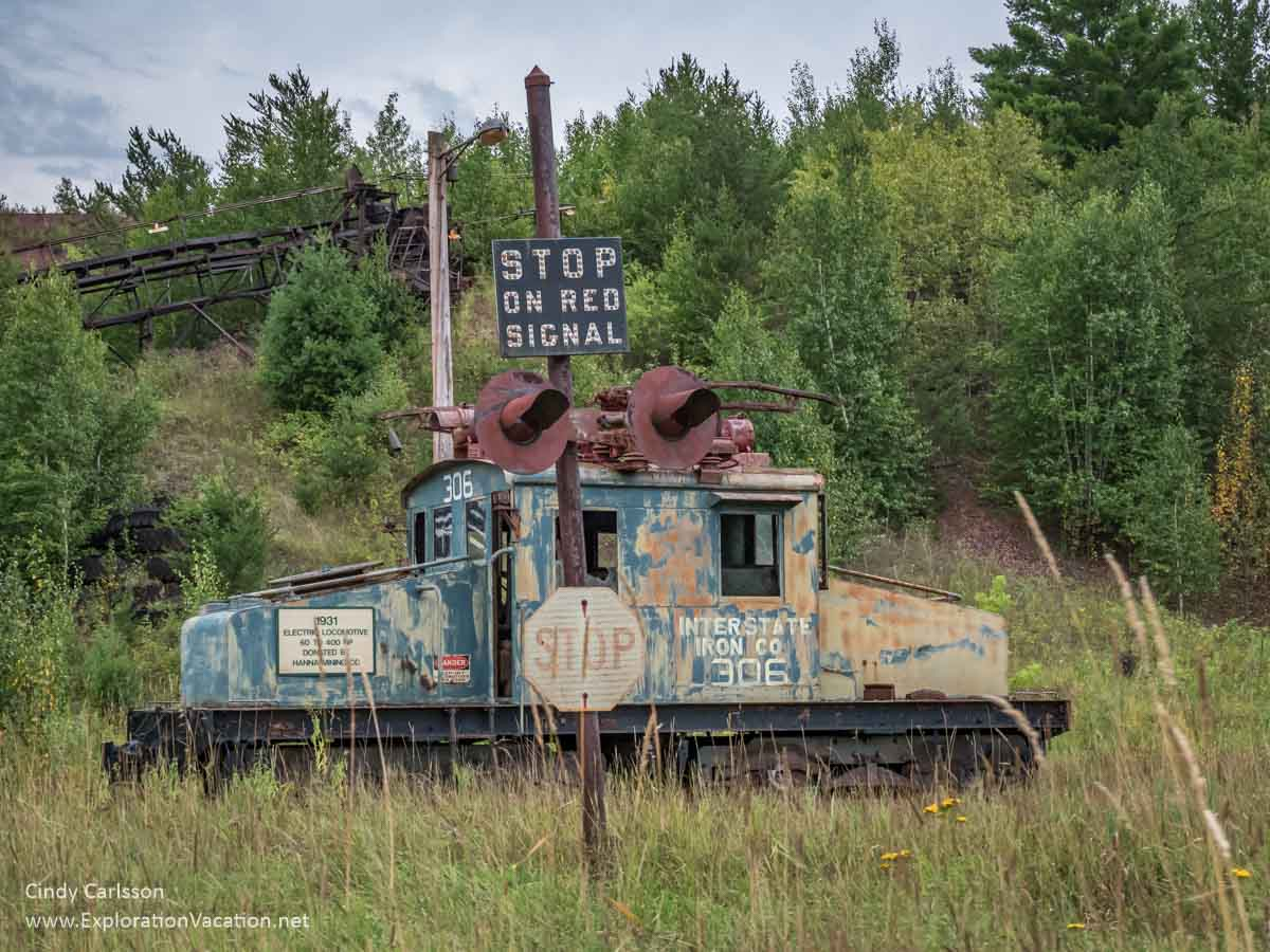 old rusty electric locomotive with a railroad sign and conveyor system