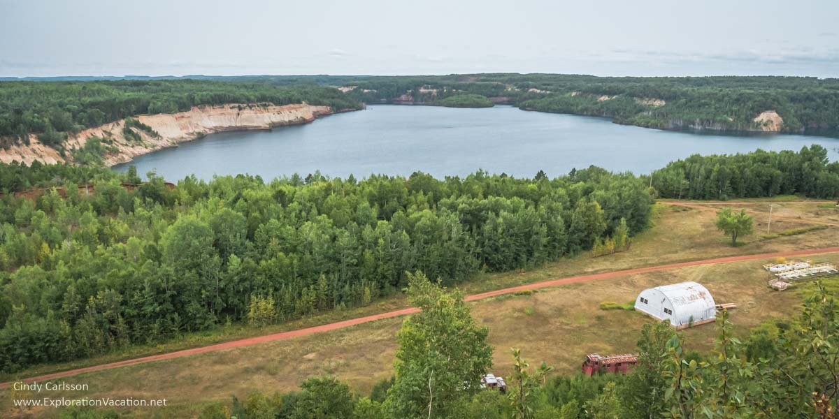 over view of lake in an ore pit with trees around it