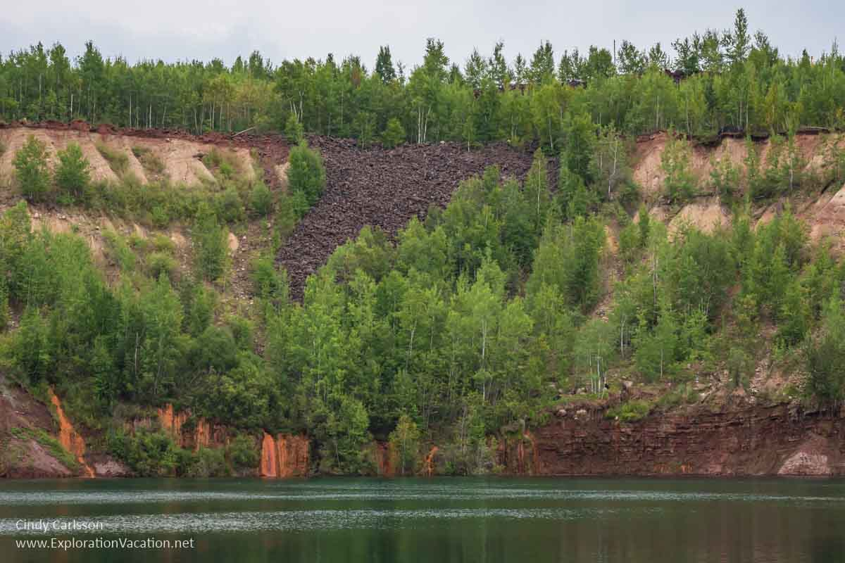 water with eroded cliff and trees above