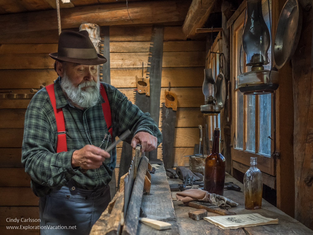 man dressed like a logger with an old-fashioned saw