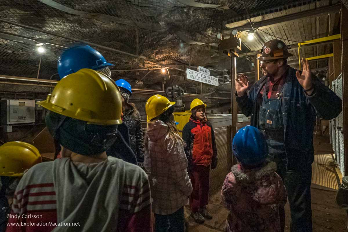 Man talking to a group of kids in hard hats in a mine