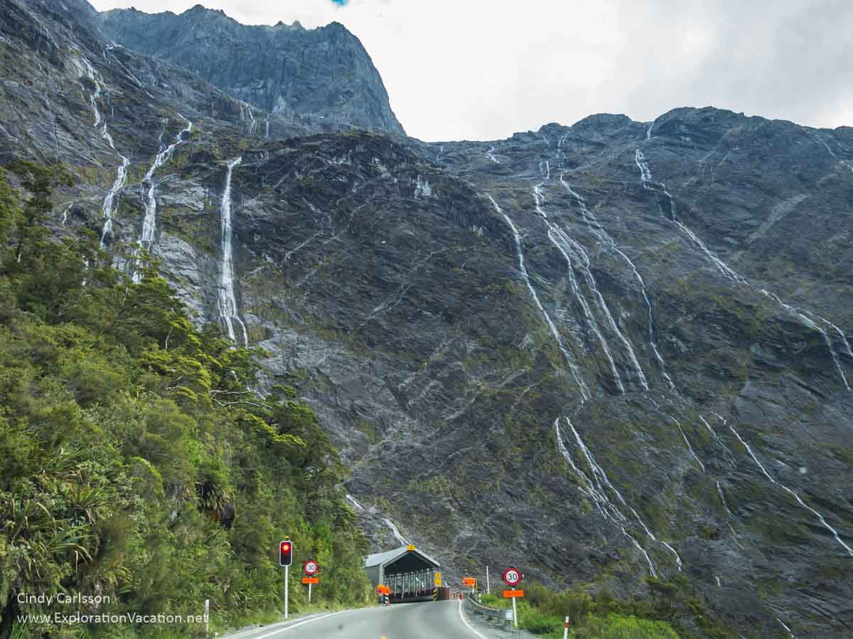 entrance to tunnel with towering mountains and waterfalls