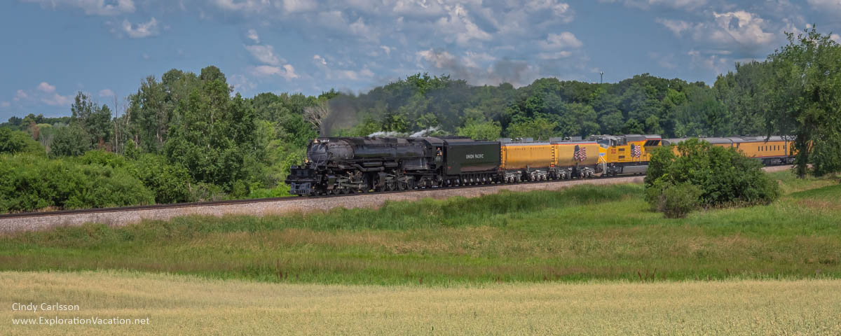 historic steam train running through rural countryside