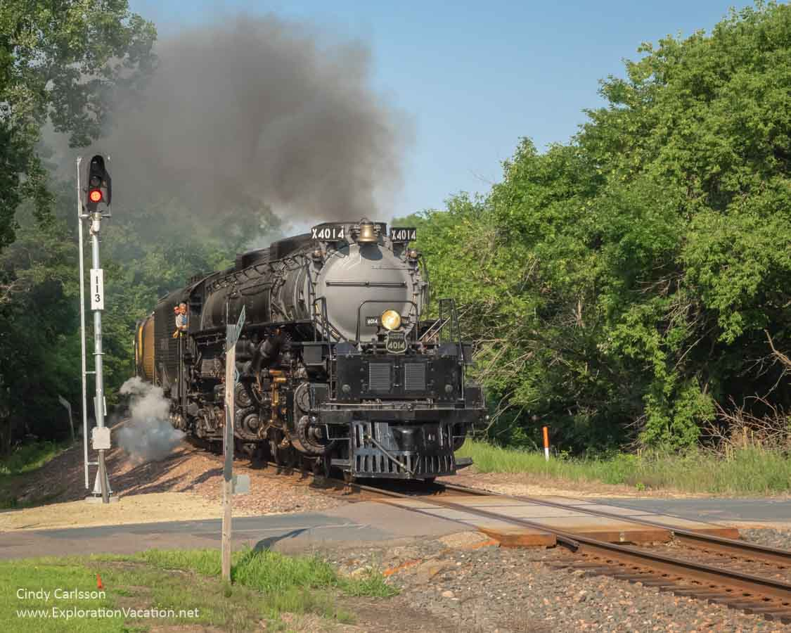 a large steam engine approaches a wooded rail crossing