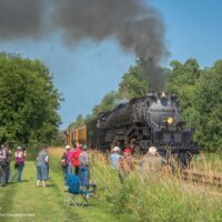 People watch a steam locomotive along a railroad track