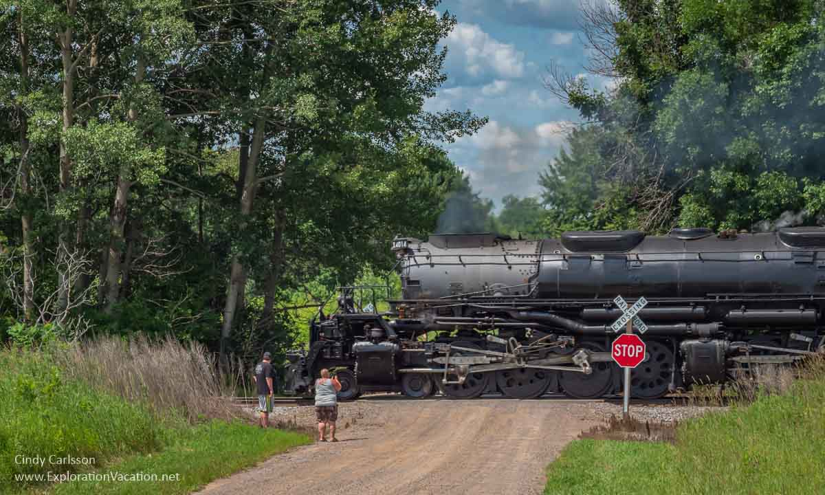rural railroad crossing with a couple people watching a steam locomotive