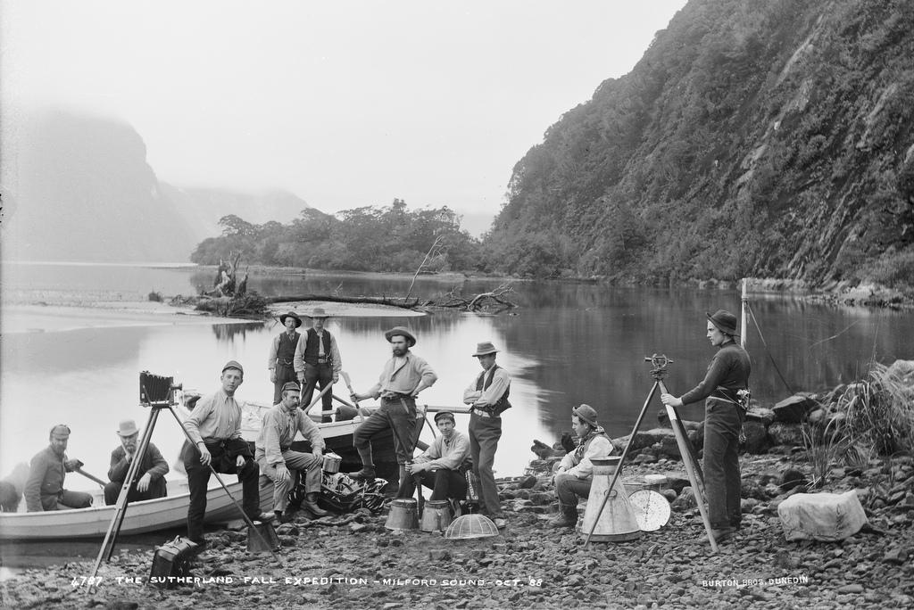 historic photo of men and boats along the shore of Milford Sound