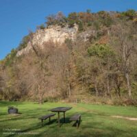 picnic tables below a large, wooded bluff