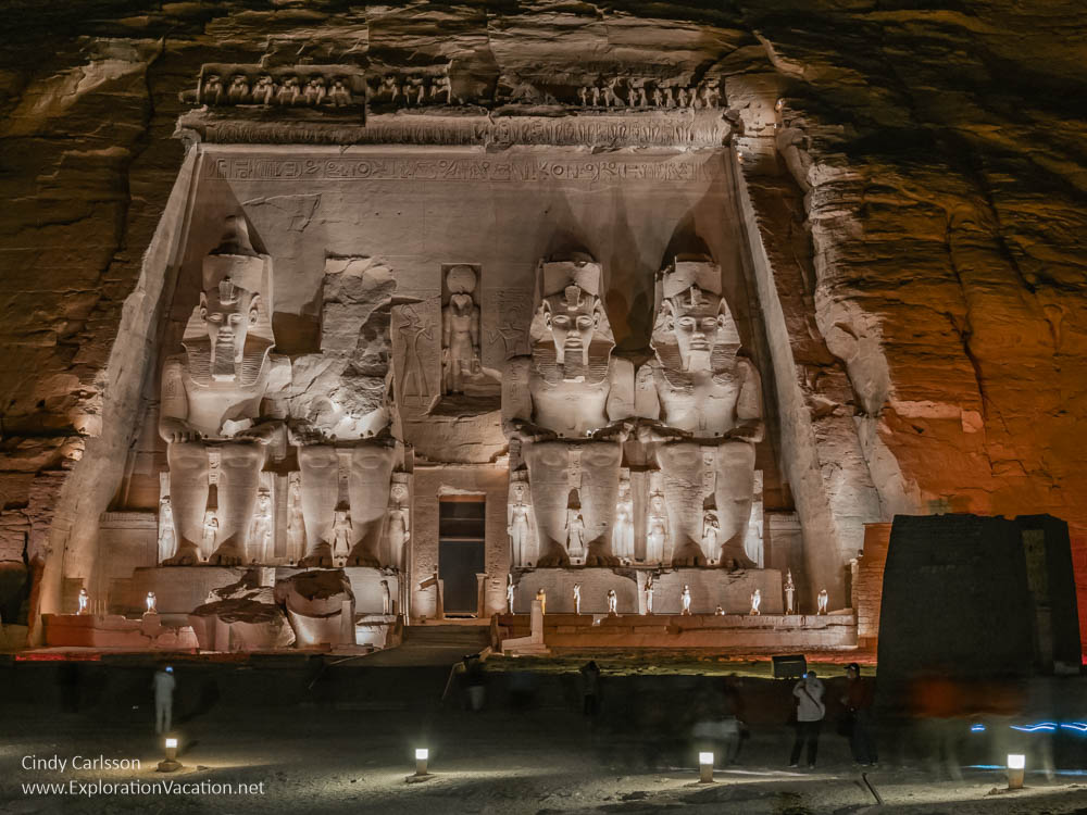 temple entrance lit at night with 4 huge statues of a pharaoh