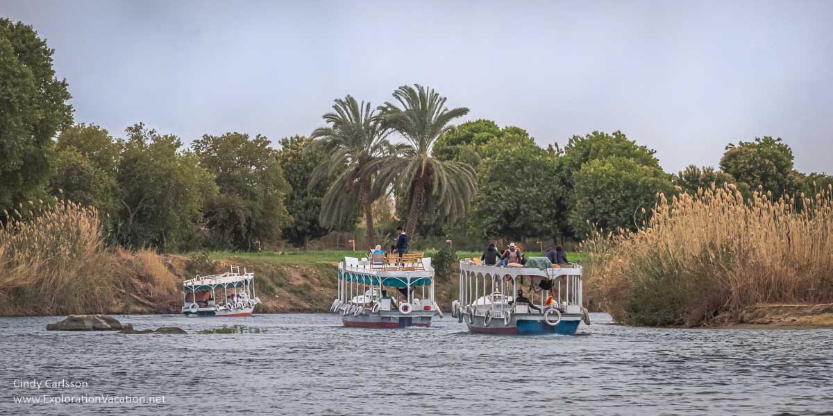 motorized tour boats ply a channel of the Nile as tourists sit on top