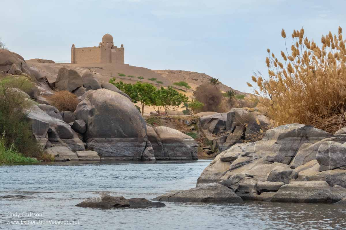 Nile flowing between large boulders with a large tomb in the distance