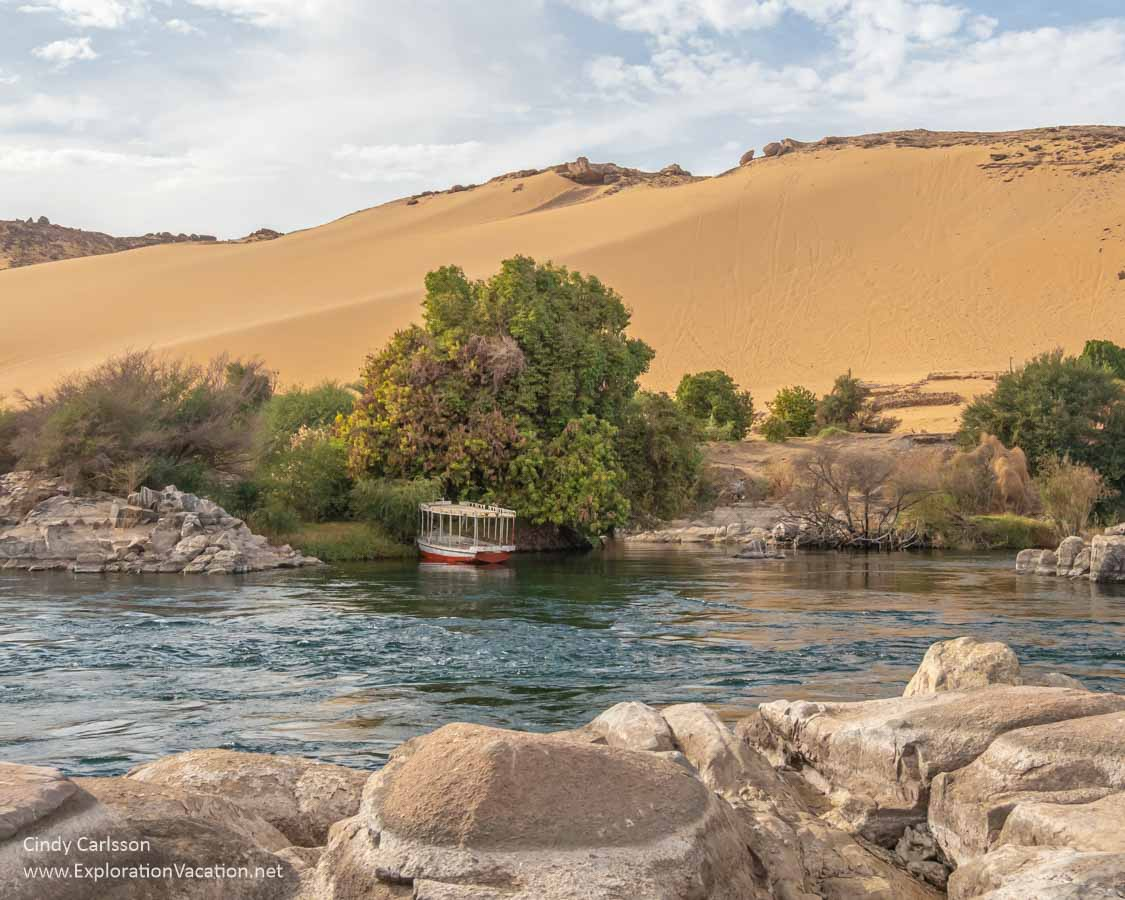 golden desert hills above the lush shores of the Nile with boulders and a motorized tour boat