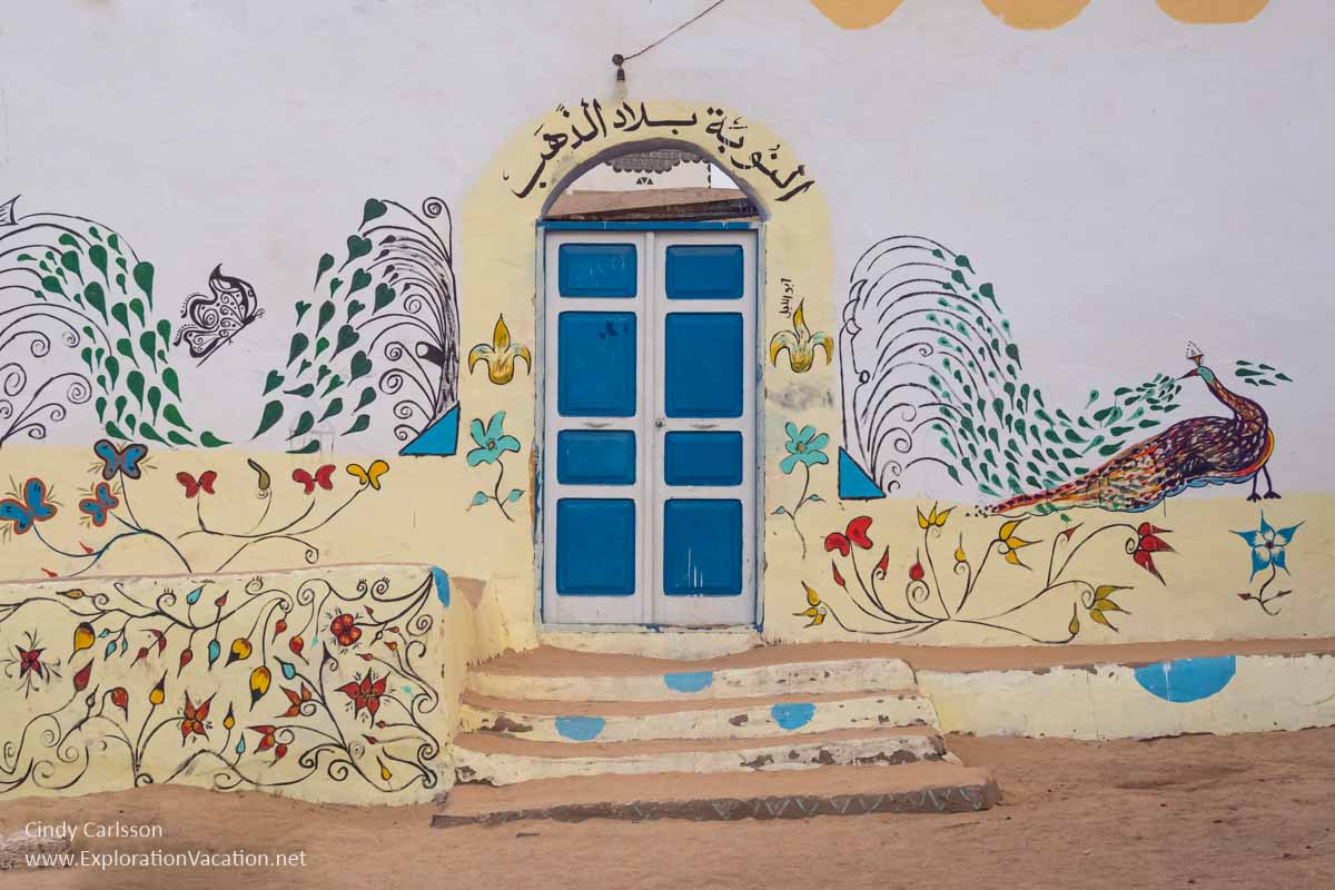 a colorful wall painted with peacocks and other designs