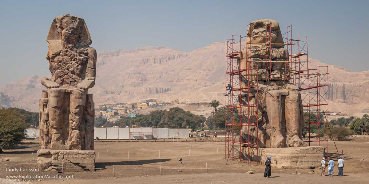 two enormous statues, one in scaffolding, on an empty plot