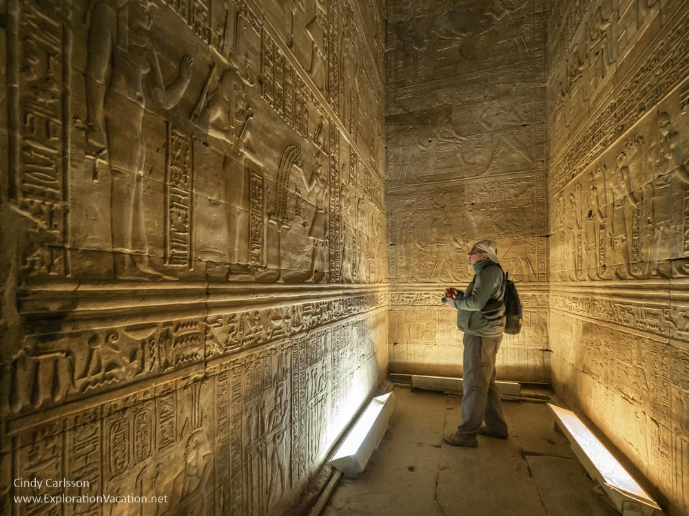 man looking at a wall filled with carvings in a small room inside a temple