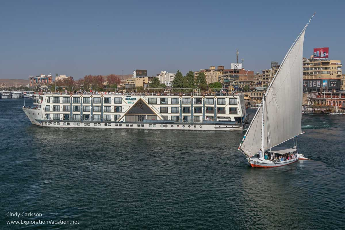 Nile river cruise ship with a felucca in a city