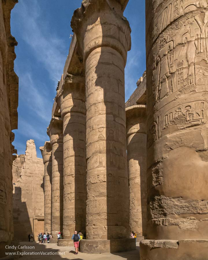 huge carved stone pillars reaching to the sky with tourists below