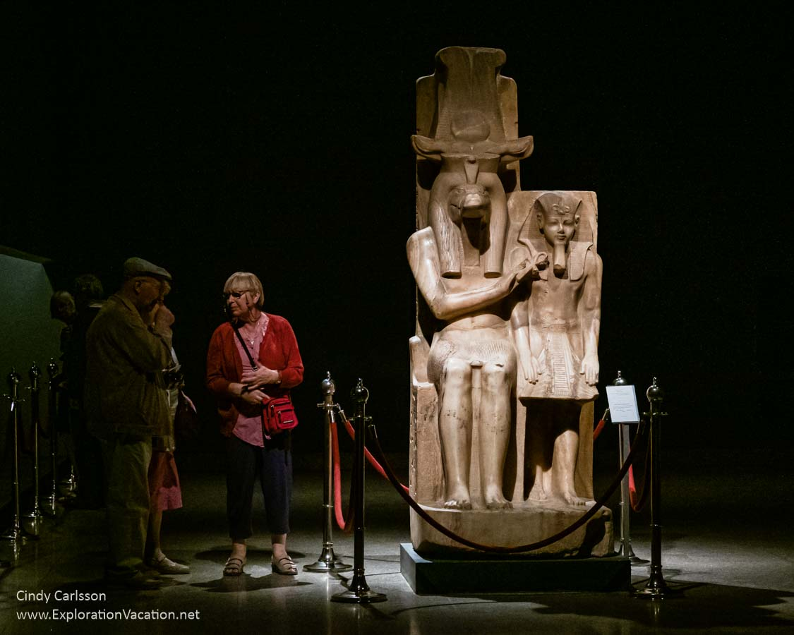 large stone statue of a god and pharaoh with people standing near it