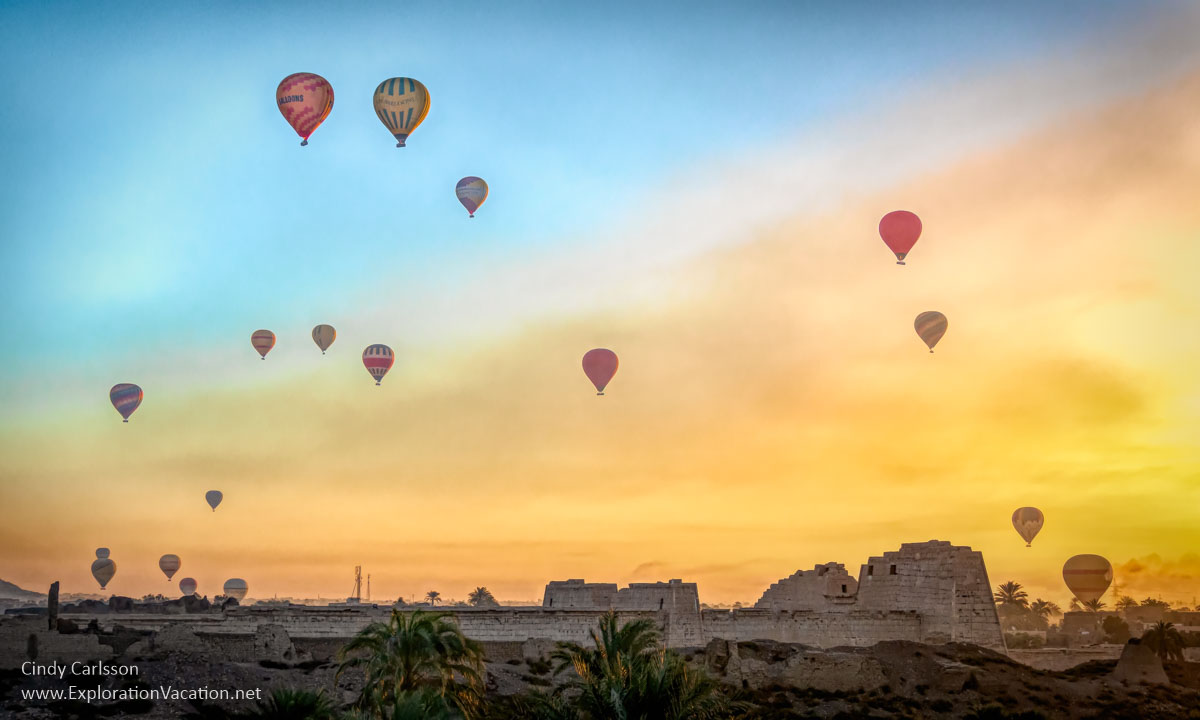 hot air balloons rise into the sky above the ruins of a temple at sunrise