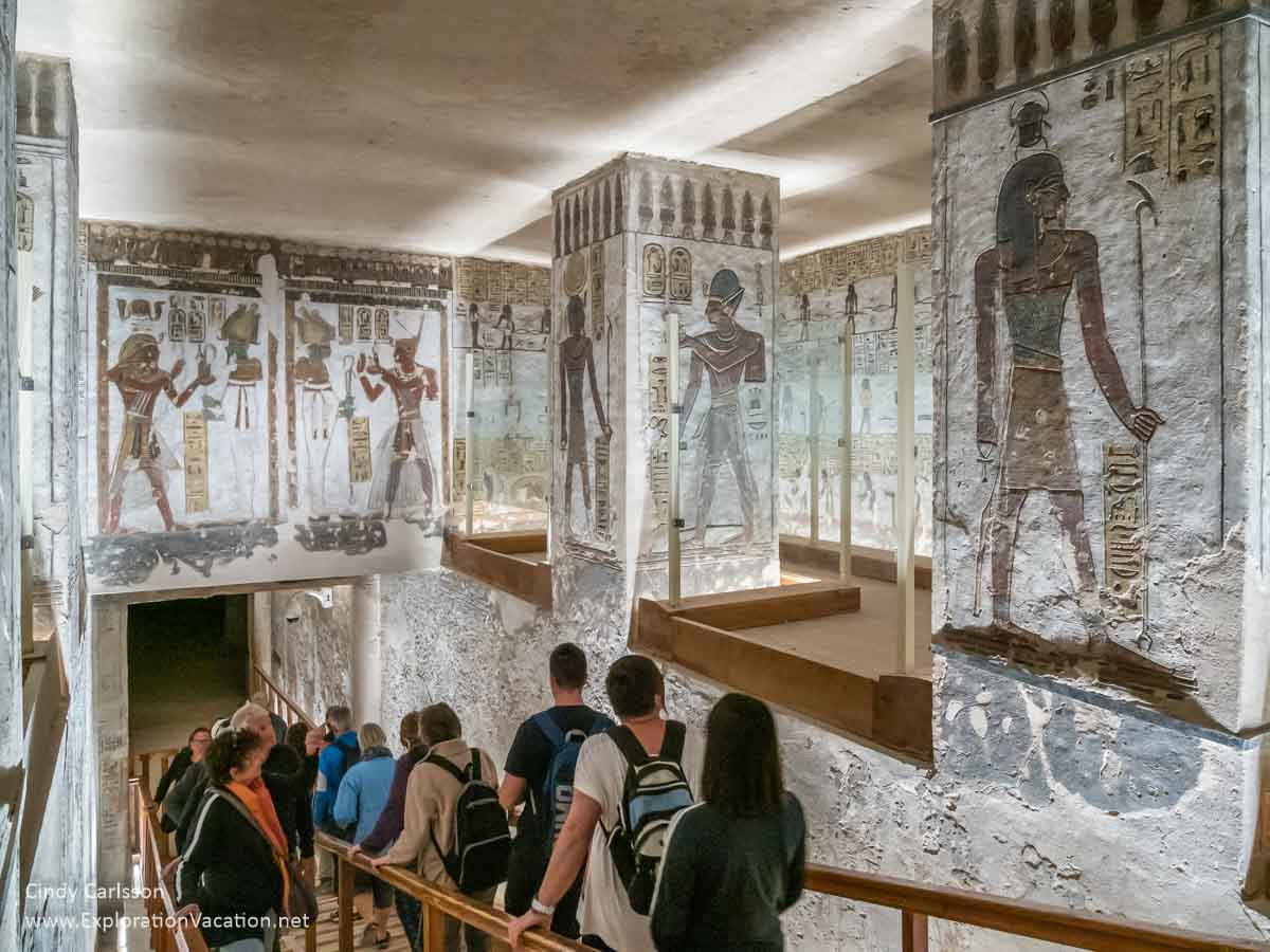 People walking down a ramp below large paintings of pharaohs and gods inside a tomb