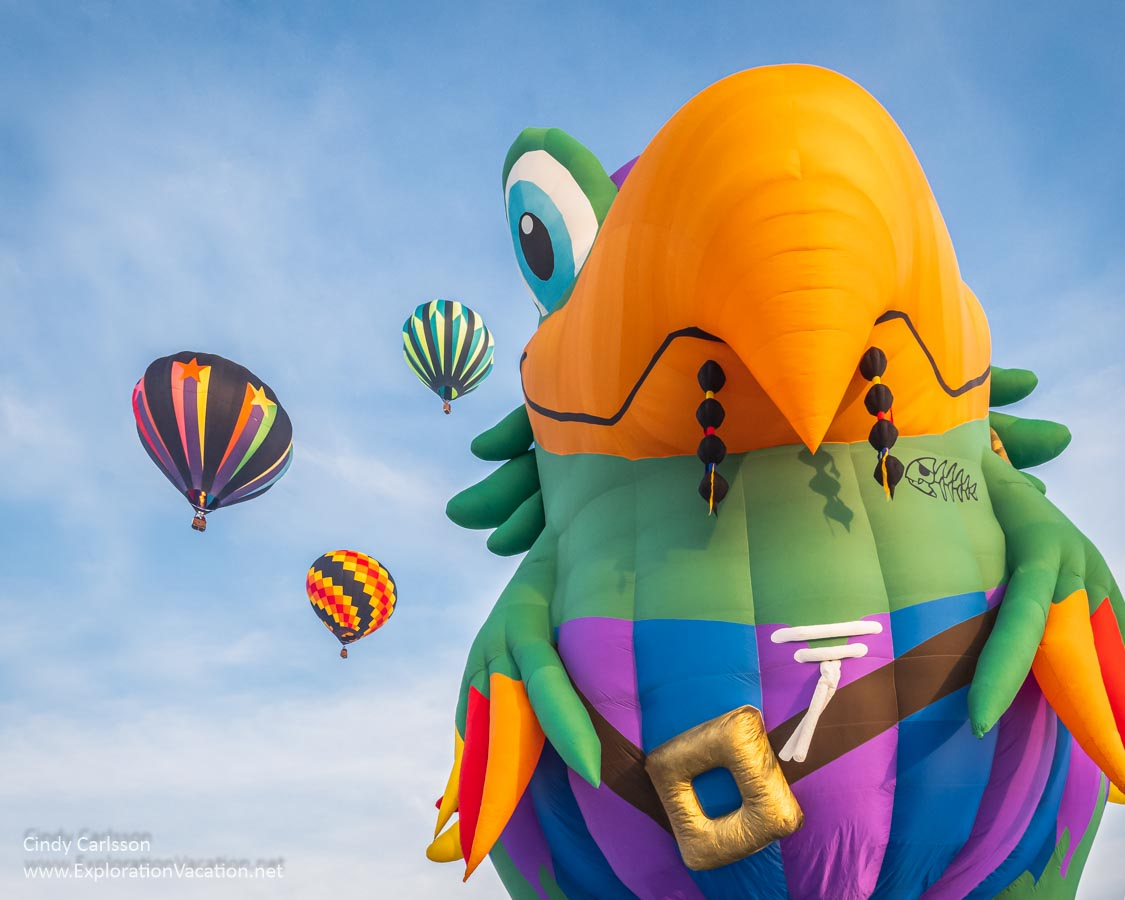 A giant hot air balloon in the shape of a pirate parrot eyes several balloons in the sky
