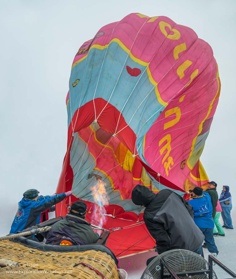 people struggle to inflate a balloon as the wind blows it around