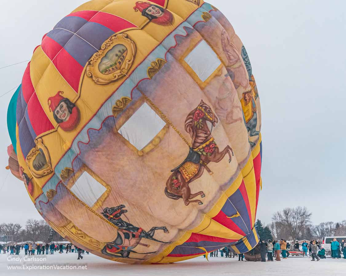 an old-fashioned hand-painted balloon begins to lift from the ground