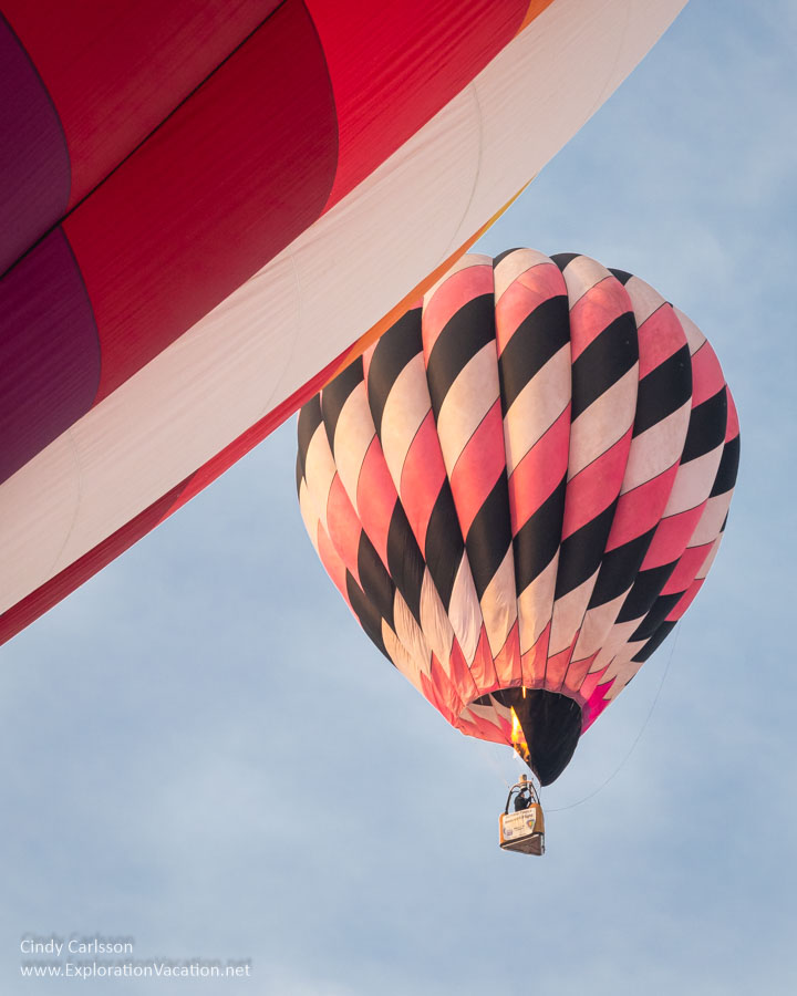 A balloon rises in the sky behind one still on the ground