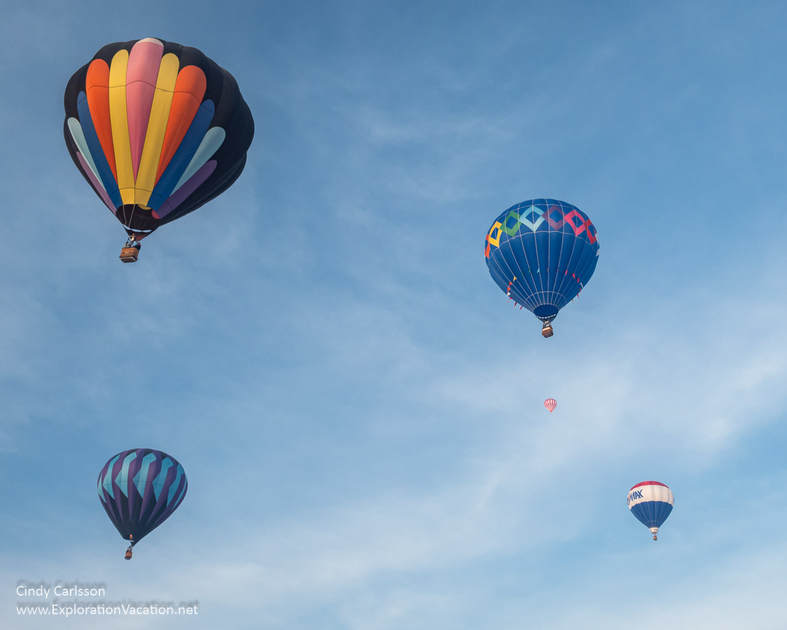five balloons float in the sky overhead