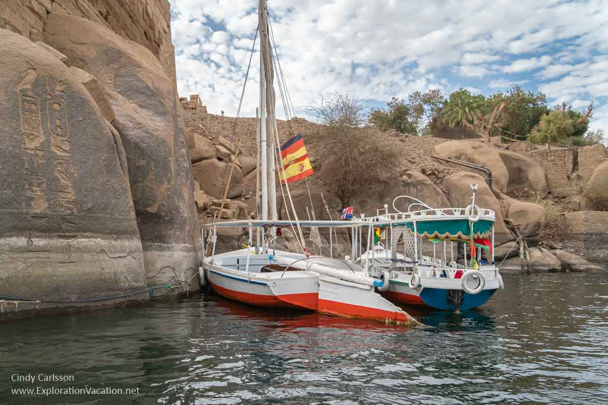 felucca and motor boat tied by boulders