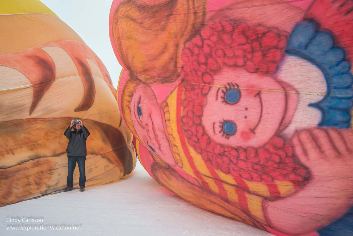 man taking pictures next to a partially-inflated hot air balloon with Raggedy Ann on the ground beside him
