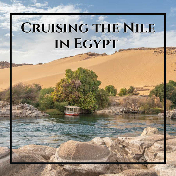 """small boat tied to a tree with large dunes behind and text """"Cruising the Nile in Egypt"""""""