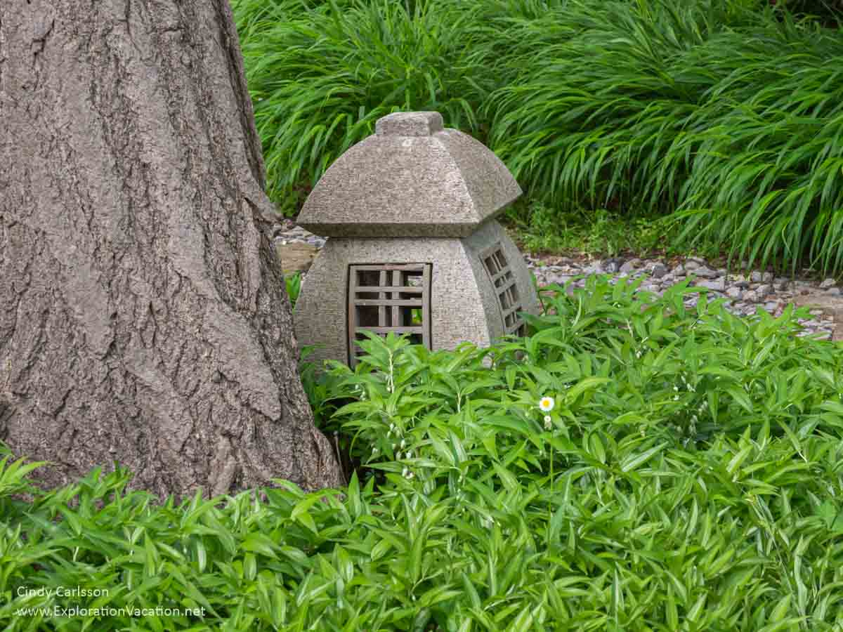 stone Japanese lantern at the base of a tree