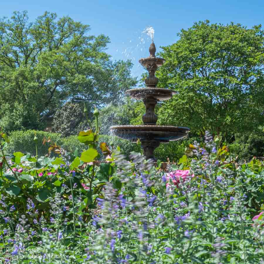 tall fountain with flowers in front and trees behind