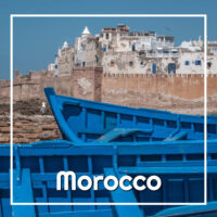 "blue boats below a white city with text ""Morocco"""