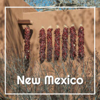 "peppers drawing by an adobe wall with text ""New Mexico"""