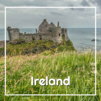 "castle ruins and sea beyond a green meadow with text ""Ireland"""