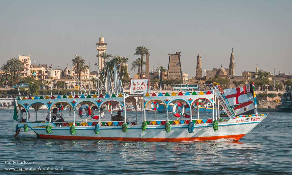 brightly colored small ferry with Luxor temple in background