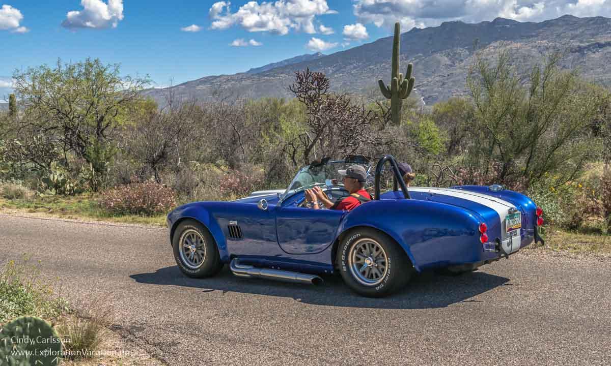 convertible driving through desert scenery