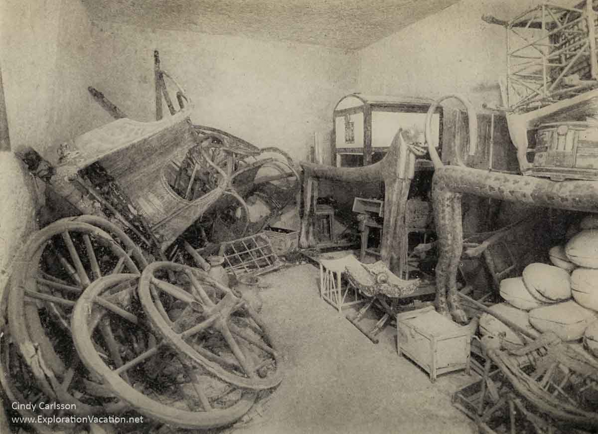 monochrome view of disassembled carriages and furniture in a plain room