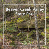 "mossy boulders along a creek with text ""Beaver Creek Valley State Park"""