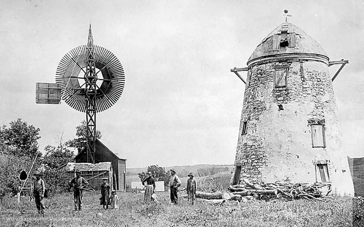 historic photo of a ruined windmill and other buildings with people