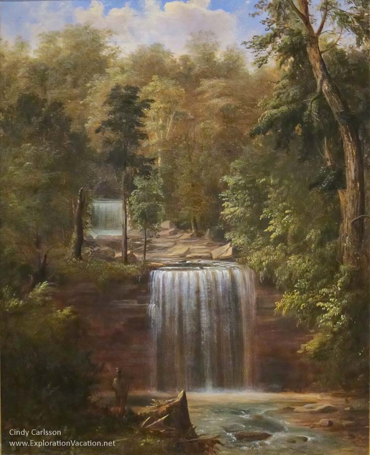 Romanticized painting of a double waterfall with an American Indian